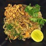 Pad Thai: Fideos de arroz salteados con tamarindo, brotes de soja, cilantro, lima, cacahuetes y
