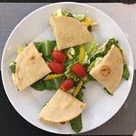 Gluten free vegetarian sandwich with hummus, olive oil, mixed greens, tomatoes, cucumbers, and p