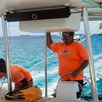 Captain Jeff at the helm with able crew member preparing drinks. Photo © David Burge