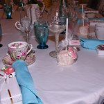 The table was beautifully set with mismatched teacups, blue glasses and wrapped utensils.