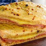 This is a pic of a Croque Monsieur. Sandwich with meat & cheese covered with melted...