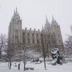 Salt Lake Temple with statute in the foreground covered in snow.