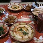 Typical hummus with falafel, salad, pita bread, and fresh granate juice