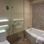 Shower on the wall of a glassed in with a door shower/bath area.