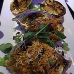 Grilled oysters topped with spinach, bacon bits and parmesan