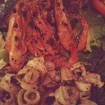 prancha com camarões grandes, lula e peixe