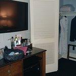 Flat screen TV over honor bar and fridge. Walk in closet with robes, umbrellas, hangers.
