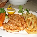 Grilled chicken breast served with fresh vegetables and chips.