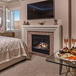 Dubai suite with window, fireplace, and king bed.