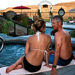 Guests on the edge of the hot tub are enjoying the water features of Cameo Heights Mansion.