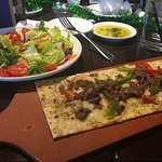 Salad and pepper and sausage flat bread