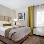 One Bedroom Suite - Separate Bedroom from Lining Area with Queen Size Bed and Large Screen TV