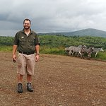 Tim Brown at a view point with Zebra in the back ground