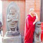 a monk looks pensively next to an ancient statue of Bhairab
