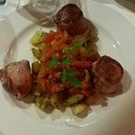 Delicious pork wrapped in bacon, paprika tomato sausage sauce and potatoes saute