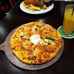 Tandoori Chicken Pizza w/ baby spinach & raita. With an orange juice.