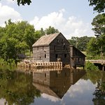 """Reflected in the still water of the pond, Yates Mill is """"pretty as a picture."""""""