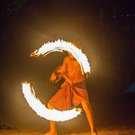 A young boy is showing off his fire dancing skills.