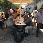 Old boys play chess at one side of the Plaza