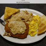 Plate of chicken fried steak with scrambled eggs and toast.