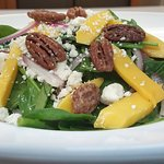 delicious spinach salad with red onion, blue cheese, mango, candied pecan with sherry vinaigrett