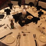 Elegant table setting with white and black linens, covered chairs w/black ties & crystal candela