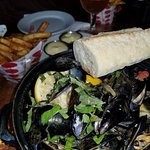 Bucket of mussels, bread, and a cone of frites.