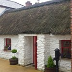 A cute cottage with a thatched roof
