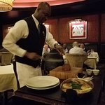 Waiter slicing our steak at tableside.