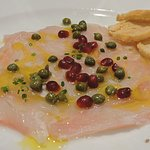 Carpaccio King fish marinated in lemon, olive oil and chilli dressing, topped with dill w crosti