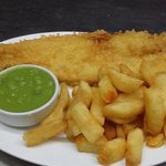 Crispy battered fish with chips and mushy peas.