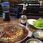 Churrasco de contra-filé com molho agridoce e acompanhamentos diversos, além da cerveja coreana