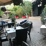 The outdoor seating, under an awning, next to bamboo plants is very pleasant.