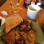 Partly eaten Frittata with home fries and spelt toast.