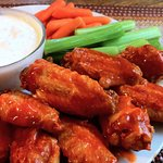 Buffalo Wings served with a side of ranch dressing.