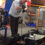 Craftsman blowing glass at end of tube as he spins glass in fire