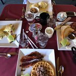 Two kinds of eggs Benedict, Black Forest ham breakfast plate, and pecan waffle with a side of ba