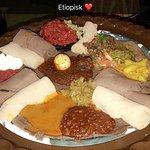 Et stort fat med ulike sauser og injera.