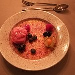 Creme brulee with rasberry sorbet and fresh berries