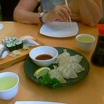 Deliciously scrumptious Gyoza dumplings, sushi selection, lemon wedge, wasabe paste, green tea