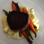 Filet mignon on a bed of mashed potatoes, asparagus, and carrots