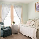 The Azalea Queen Bed Suite Sitting room with day bed, mini-fridge and flat screen television.