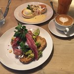 Avocado on toast with bacon, Eggs royale in the background, Flat white