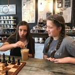 Zoe and Zia enjoying a game of chess and ice coffee