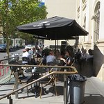 Outside seating on La Trobe Street. Entrance to cafe to RHS.