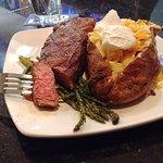 The sirloin strip steak with loaded baked potato and asparagus.