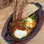 Shakshouka is a dish of eggs poached in a sauce of tomatoes, chili peppers, and onions, often sp