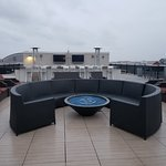 Rooftop lounge area with grills, tvs, tables, seating, and firepits.