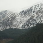 snow covered mountains behind loch