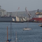 Fleet Auxiliary ships under refit & a sloop passing in front.